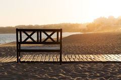 Bench on the beach at yellow sunset. Stock Photos