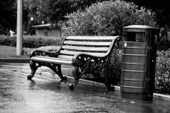 Bench and bin. Wet after the rain, are in the park. Black and white Stock Images