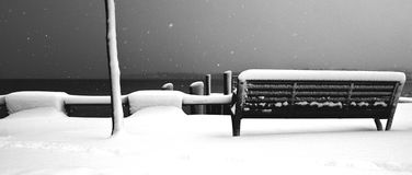 Bench. Black and white bench in a snowy day in Mondsee Stock Image