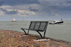 A bench and the boat in the Netherlands Stock Image