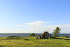 Bench and bonfire set near sea. Bench and a bonfire pile at a grass field near sea Stock Image