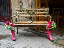 Bench with boots and flowers in the streets of Barcelona Stock Photos