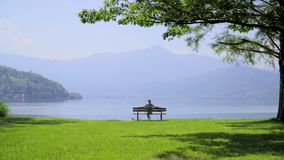 Bench With Breathtaking View. Silhouette of a girl sitting on a bench and enjoying breathtaking peaceful landscape. Alone woman on chair sightseeing mountain stock footage