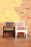 Bench and brick wall. Wooden chairs royalty free stock photography