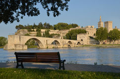 Bench, bridge and Pope's Palace in Avignon. A bench in park in front of the famous bridge and Pope's Palace in Avignon, France Royalty Free Stock Image