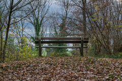 A bench with brown leaves on the ground in fall. With a great view of the valley Royalty Free Stock Photos