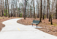 Bench By Concrete Walking Path In Winter Park Royalty Free Stock Photos