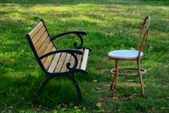 Bench and chair on the green grass Stock Images