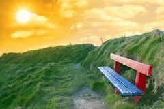 Bench on a cliff edge at sunset Stock Image
