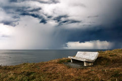 Bench on cliff with storm over sea Stock Photo