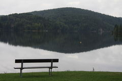 A bench close to a lake. Bench at a lake in Norway. adjacent to the lake is a mountain. lake is located above a power plant and tend to be mirrored. water rapids Stock Images