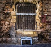 A bench and a closed window. Old doors of Valletta, Floriana, Birgu, Kalkara, Bormly. Malta. Old walls of the old town of the fortress in the city of Valletta Royalty Free Stock Photos