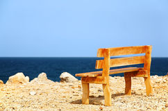 A bench on a coast. A yellow wood bench on a coast Royalty Free Stock Photo