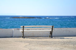 Bench on the coast of Aegean Sea. Royalty Free Stock Photography