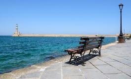 Bench con la opinión sobre el faro de la ciudad de Chania en la isla de Creta Imagen de archivo libre de regalías