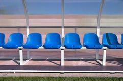 Bench con los asientos plásticos rojos para los jugadores en el estadio Fotos de archivo