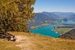 Bench con una vista del lago e delle montagne immagini stock libere da diritti