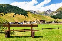 Bench con una vista di Livigno e delle alpi italiane Immagine Stock