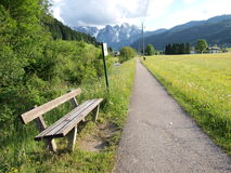 Bench on the country road. To the Alps. Shot in Gosau village,  salzkammergut of Austria Royalty Free Stock Images