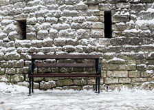 Bench covered with snow in background of the fortress wall Stock Photo