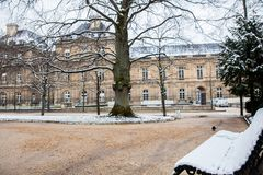 Bench covered with snow at the Luxembourg Palace garden in a freezing winter day. Day just before spring royalty free stock photography