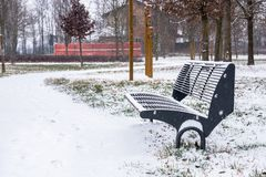 Bench Covered in Snow in a Public Park. Stylish Metal Bench Covered in Snow in Park during a Snowstorm Royalty Free Stock Photos