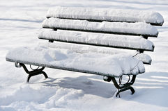 Bench covered in snow after snowfall Stock Images