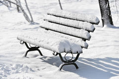 Bench covered in snow after snowfall Stock Photo