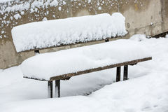 Bench covered with thick layer of snow Royalty Free Stock Images