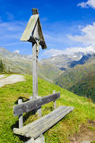 Bench and cross at mountains Royalty Free Stock Photo