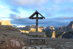 Bench with crucifix at Bullelejoch and Sexten Dolomites mountain panorama in South Tyrol Stock Photos