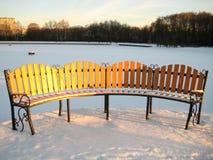 Bench dans les faisceaux du soleil de l'hiver en stationnement d'a photographie stock