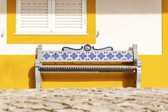 Bench decorated with traditional tiles called azulejos, Portugal. Bench decorated with traditional tiles called azulejos in front of yellow house, Portugal Stock Image