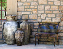 Bench and Decorative Urns. A metal bench and a trio of large, decorative urns front the stone wall of a home in the American southwest Stock Image