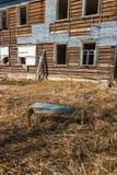 Bench delante de un edificio de madera abandonado y dilapidado con las ventanas vacías Foto de archivo libre de regalías