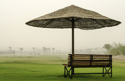 Bench in desert under an umbrella from sun. Royalty Free Stock Photo