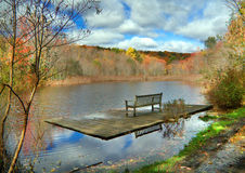 Bench on Dock. Wooden dock with bench with lake view in autumn Stock Photo