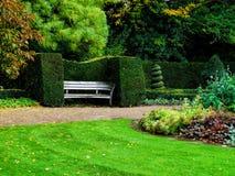 Bench em arbustos agradavelmente aparados no parque do regente, Londres Projeto da paisagem Fotos de Stock Royalty Free