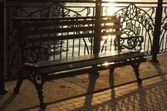 Bench on the  embankment in sun beams Royalty Free Stock Photography