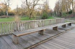 Bench en el fondo de un claro con un río Imagenes de archivo
