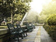 Bench en el parque con el sprinker del agua y la luz de la mañana Fotos de archivo libres de regalías