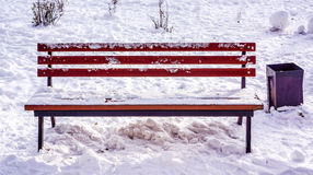 Bench en el parque de la ciudad del invierno que se ha llenado de nieve con la cesta negra cerca de él Imágenes de archivo libres de regalías