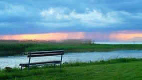 Bench en la costa del lago poco antes la tormenta fotografía de archivo