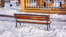 Bench en parque del invierno con una linterna en un fondo Imagenes de archivo