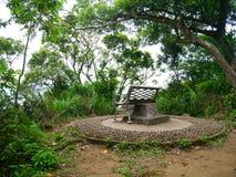 Bench en una plataforma de piedra redonda rodeada por los árboles imágenes de archivo libres de regalías