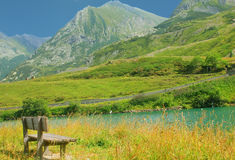 Bench facing the mountains. A bench facing the mountains and a lake Royalty Free Stock Photography
