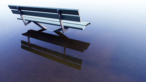 Bench in a flooded park Royalty Free Stock Photos