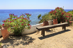 Bench and flowers on background of Aegean Sea. Royalty Free Stock Photo