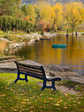 The bench. A bench in the foreground and autumnal scene on the background royalty free illustration