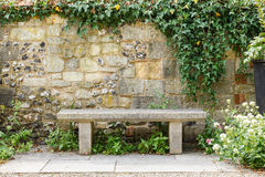 Bench in formal garden. Bench in a formal garden with an old stone wall Stock Photos